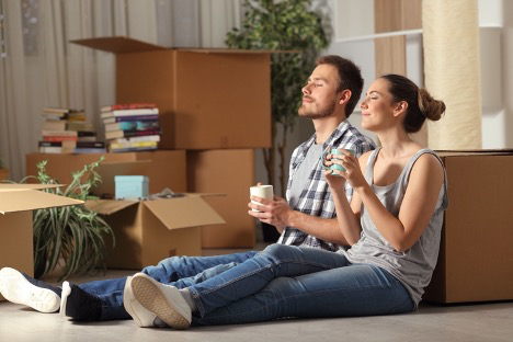 A man and woman leaning on a moving box enjoying a cup of coffee